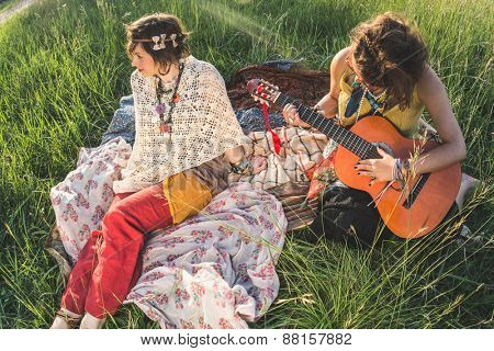 Two young woman singing and playing on guitar