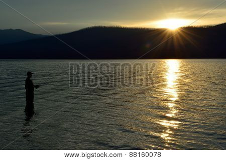 Fisherman Fishing In Mcdonald Lake In Glacier National Park At Sunset