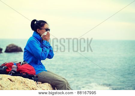 hiking woman sit on seaside rock