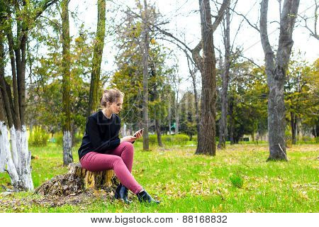 Beautiful Girl Sitting On A Stump In The Park With Smartphone