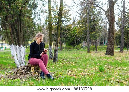 Beautiful Girl Sitting On A Stump In The Park With Your Smartphone