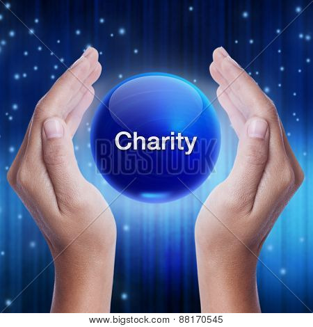 Hand showing blue crystal ball with charity word.