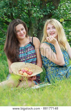 Blonde and brunette sitting on grass in farm summer arboretum