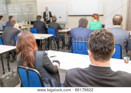 Rear View Of Business People Listening Attentively While Sitting At The Classroom