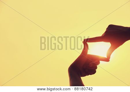 shape making of hands against bright sea sunset and sunny golden way at water