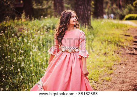 happy curly kid girl in pink princess dress dancing in summer forest