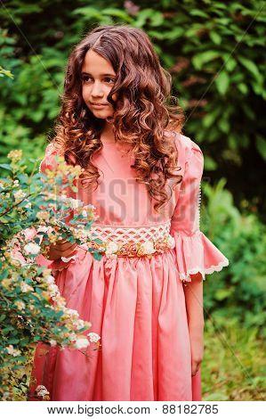 summer vertical portrait of happy child girl in pink fairytale princess dress