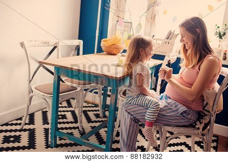 happy pregnant mother playing with her baby daughter at home in kitchen