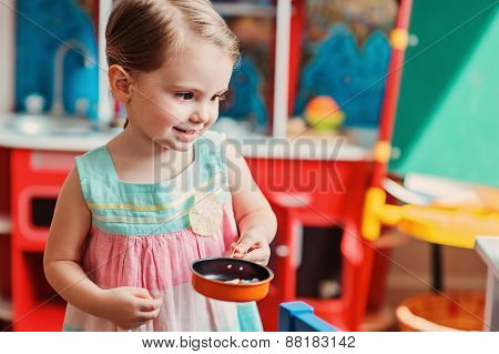 cute toddler girl playing toy kitchen at home