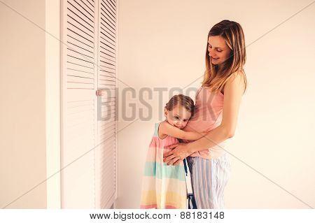 Happy pregnant mother and child daughter having fun at home