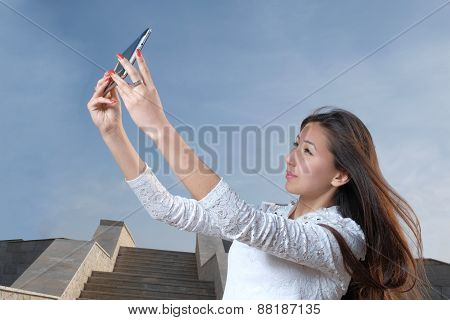 Casual japanese women with long hair do selfie in city park against steps and clear blue sky light h