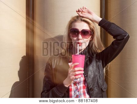 Beautiful sexy blonde with sunglasses drinking beverage through a straw on a hot summer day near the