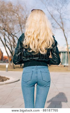 Pretty young fashion sexy girl with beautiful long blond hair on the road in evening summer time hav