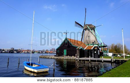Windmills And River And Boat In Holland