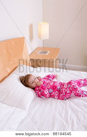 Small Girl In Pink Pajamas Lying Resting On A Bed