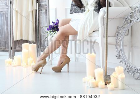 Beautiful Young Bride With A Wedding Bouquet Sitting At The Sofa