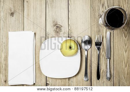 A white plate, cutlery set, a white napkin dining room, an apple and  a wine glass on a wooden backg