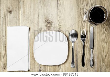 A white plate, cutlery set, a white napkin dining room and  a wine glass on a wooden background