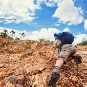 stock photo of khakis  - Close up of a man climbing up red rock dressed in hiking shoes khaki color shorts and t - JPG