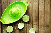 pic of juicer  - green limes with green manual juicer on the table - JPG