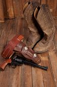 stock photo of revolver  - A revolver with holster and cowboy boots on a wooden background - JPG
