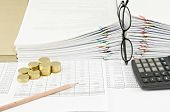 picture of spectacles  - Brown pencil and gold coins with vertical spectacles at pile of paperwork as background - JPG