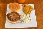 stock photo of crab-cakes  - Fried mixture of lump crab meat and special seasons on toasted bun and served with coleslaw and sweet potato chips - JPG