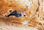 image of struggle  - Young female rock climber struggling to make next movement up - JPG