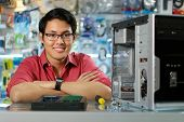 stock photo of ram  - Young asian shop owner working in computer store repairing computer and adding ram to pc. Portrait of man smiling at camera
