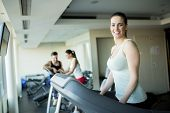 stock photo of treadmill  - Young woman training on a treadmill in the gym - JPG