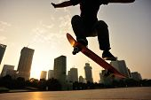 picture of skateboard  - young skateboarder skateboarding ollie trick at sunrise city - JPG