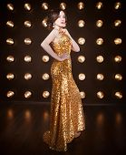 picture of superstars  - Superstar woman wearing golden shining dress posing - JPG