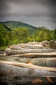 stock photo of rainy weather  - Rainy weather over rural landscape with wooden logs in the foreground - JPG