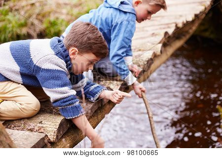 Two Boys On Wooden Bridge Playing With Sticks In Stream