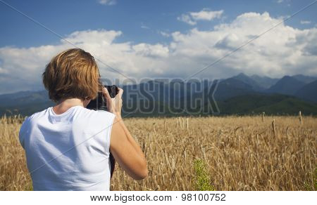 Happy traveler girl photographing ripe wheat field in bright sun rays, autumn harvest season, travel and tourism concept