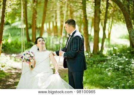 Newlyweds On Swing On Wood