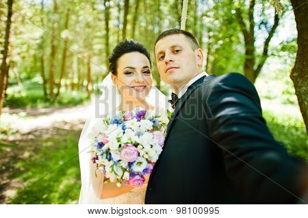Gorgeus Wedding Couple On Green Sunny Forest. Groom Doing Selfie