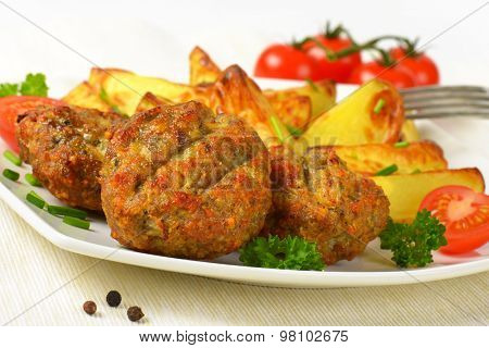 detail of roasted potatoes and fried meatballs on white plate