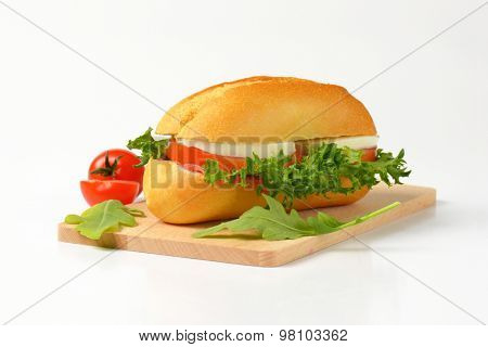 close up of bun sandwich with mozzarella cheese and fresh vegetables on wooden cutting board