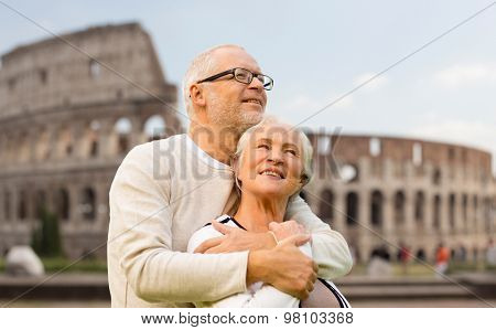 family, tourism, travel and people concept - happy senior couple over coliseum in rome, italy
