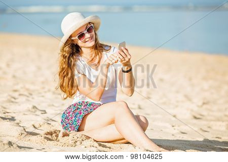 Beautifil young woman on the beach at sunny day with mobile phone