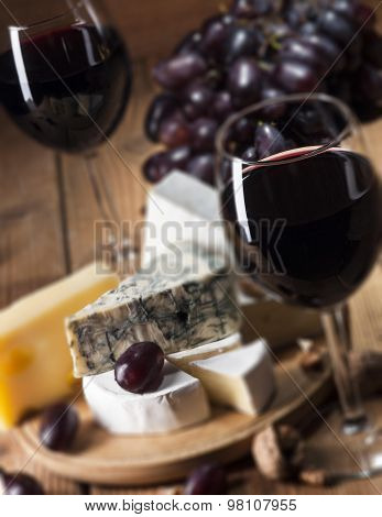 Red wine with various types of cheese on wooden background