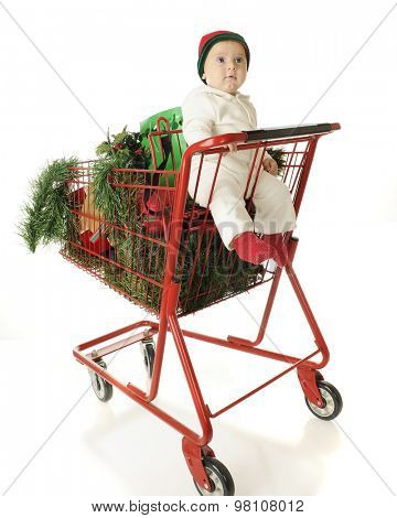 An adorable baby boy riding in the child's seat of a red shopping cart filled with Christmas gifts and decor.  On a white background.