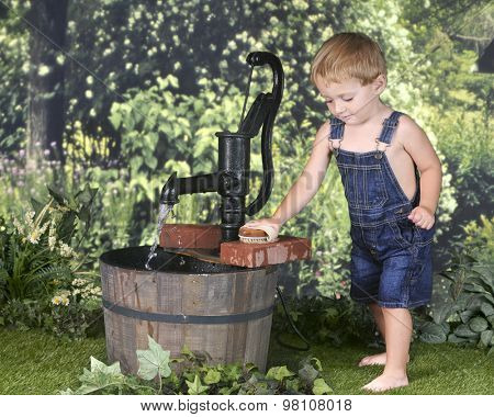 An adorable barefoot 2 year old scrubbing bricks outside by an old water pump.