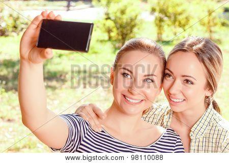 Two girlfriends doing selfie in park