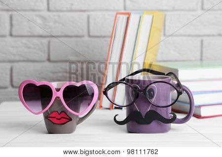Books and cup with mustache and lips on wooden table on brick wall background
