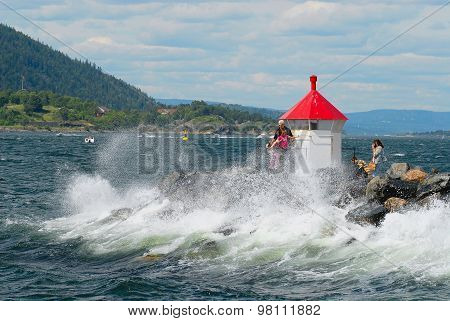 People make travel photos at the lighthouse with the coming wave in Frogn, Norway.