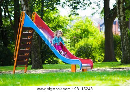Little Girl Sliding On A Playground