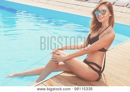 Pretty smiling lady at poolside