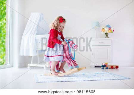 Little Girl Riding A Toy Horse